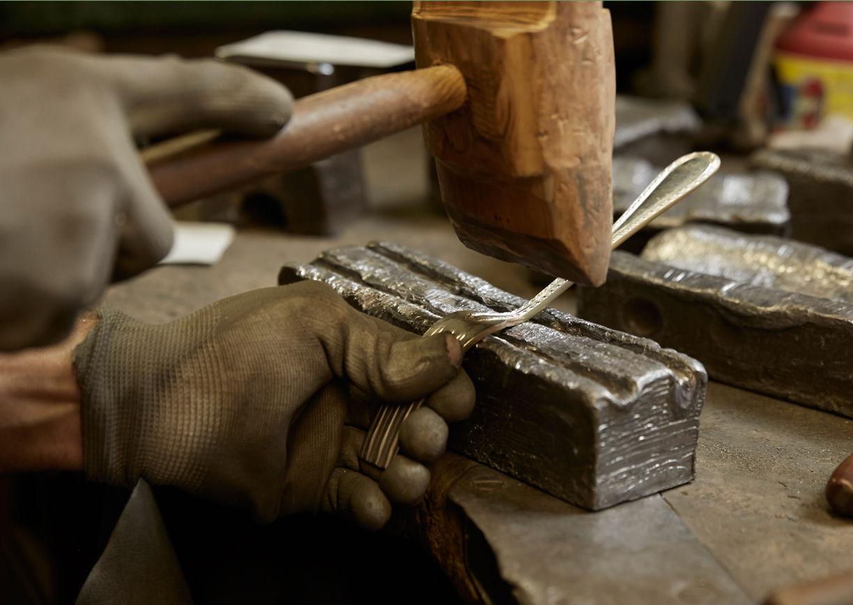 Hand beschlägt mit Holzhammer Silbergabel
