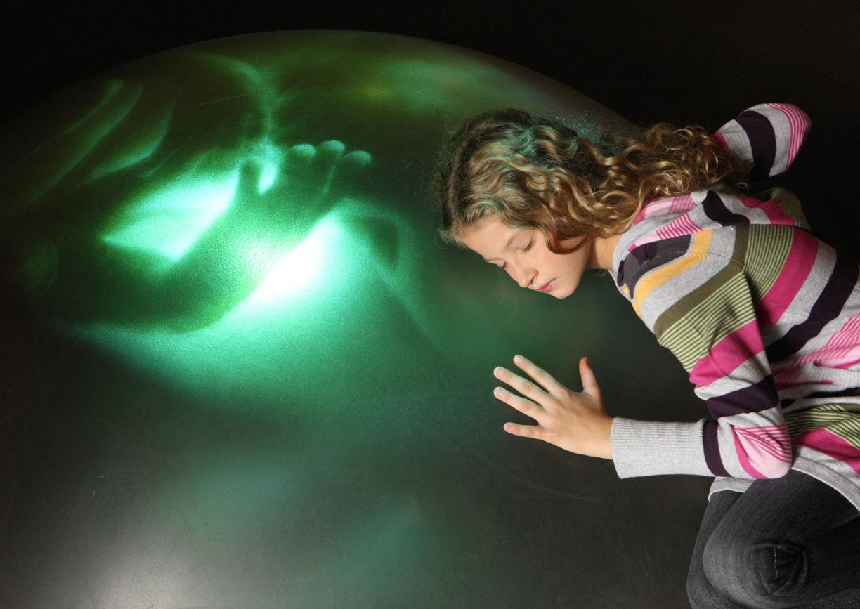 Haus der Musik, Mädchen legt Ohr an Leinwand mit Embryo.