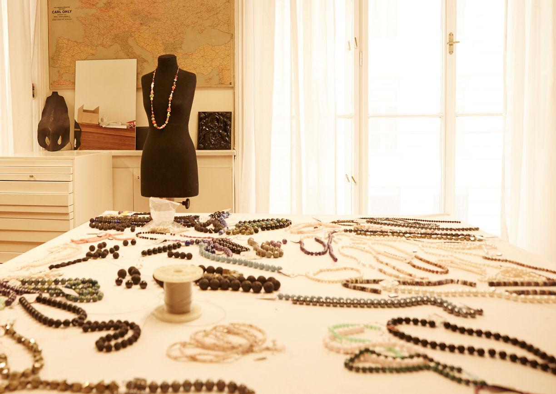 Perlenketten auf Tisch verstreut liegend, Ateliertisch mit Schmuckstücken.